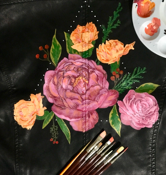 Pink and orange rose florals painted onto a black leather jacket.