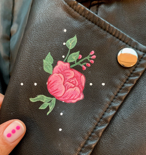 Flower painted on the lapel of a black leather jacket.