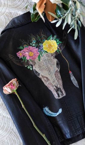Cows head painting and florals on the back of a black leather jacket.