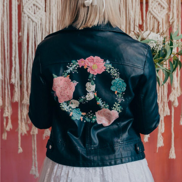 Girl wears black leather jacket with floral peace symbol painted on the back.