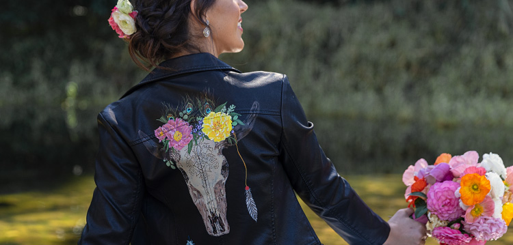 Girl holds bouquet of flowers and wears black leather jacket with cow skull and florals.
