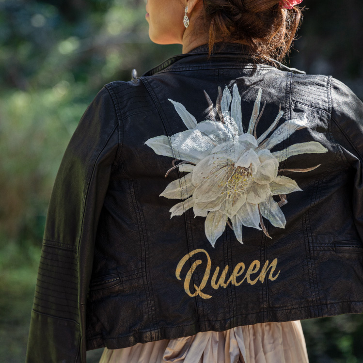 Girl wears black leather jacket with big white flower and words 'Queen' painted on the back.,