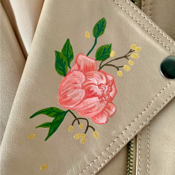 Painted flower on lapel of tan leather jacket.