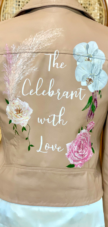 Tan leather jacket with 'The Celebrant with Love' words and florals painted on the back.
