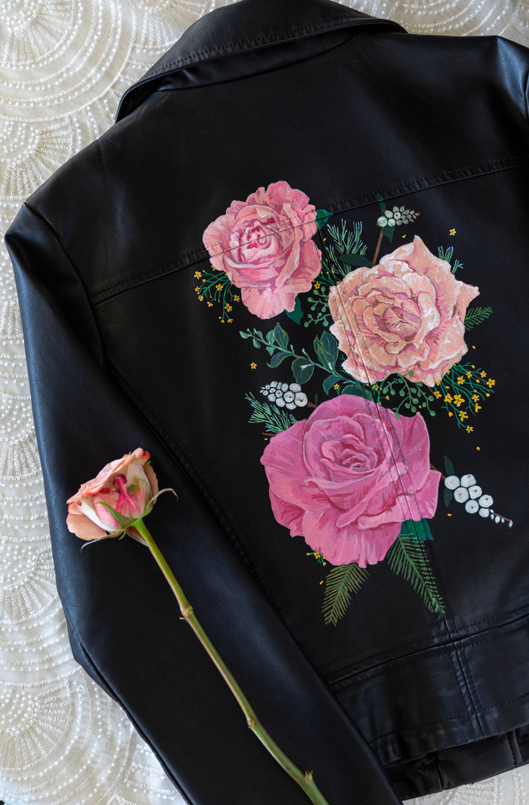 The back of a black leather jacket with rose florals painted on.