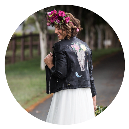 Image in circle of girl with black leather jacket and flowers in her hair.